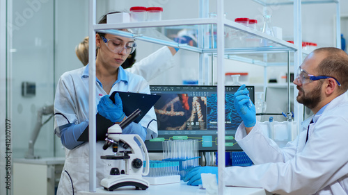 Obraz na plátně Diverse team of biochemistry scientists developing drugs agains new virus, doctor checking samples while nurse taking noters on clipboard in modern equipped laboratory