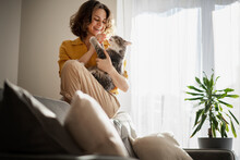 Beautiful Cheerful Young Woman With A Cute Gray Cat In Her Arms At Home In The Interior, Friendship And Love For Pets