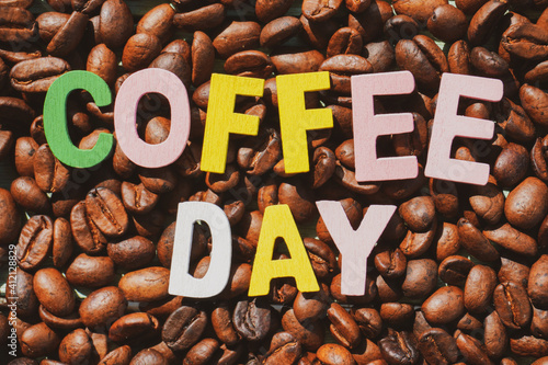Canvas Coffee Day alphabets on the roasted coffee beans background.