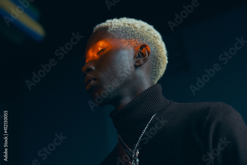 Valokuva portrait of a dark-skinned handsome guy with white hair dressed in a brown sweat