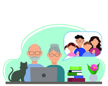 Grandparents Are Sitting At A Table With A Laptop, Chatting With Their Son And His Family On The Internet, On The Table: A Flower, A Stack Of Books And A Cat