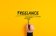 Male Hand Writing Freelance On Yellow Background. Freelance Job Or Working As A Freelancer Concept..