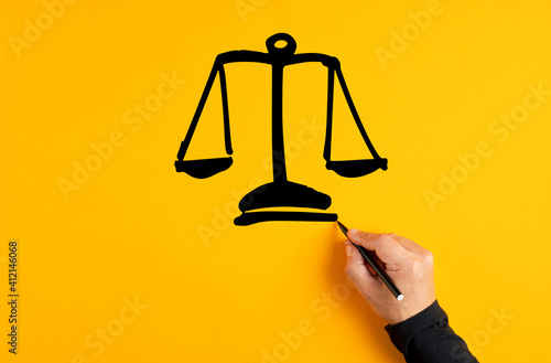 Male hand drawing a justice scale on yellow background Fototapeta