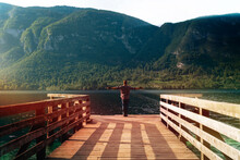 """Man Alone Standing On A Wooden Pier At A Mountains Over Water. Summer Sunset Time. Travel And Freedom Concept """"Bohinjsko Jezero"""" Slovenia"""