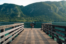 """Man Dance Alone On A Wooden Pier At A Mountains Over Water. Summer Sunset Time. Travel And Freedom Concept """"Bohinjsko Jezero"""" Slovenia"""