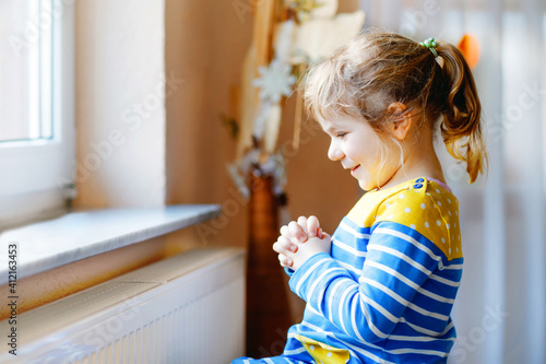 Obraz Cute toddler girl praying to God at home. Child using hands for pray and thank Jesus. Christian tradition. - fototapety do salonu