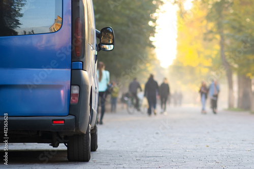 Papel de parede Passenger van car parked on a city alley street side with blurred walking pedestrians in autumn