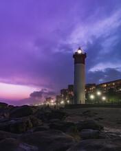 Lighthouse By Illuminated Buildings Against Sky At Dusk