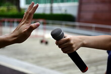 Close-up Of Hand Holding Microphone By Man Showing Stop Gesture