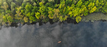 Top Aerial View Of The River Along Which A Small Orange Kayak Floats. Green Trees Grow On The Shore. Banner. Ukraine, Europe