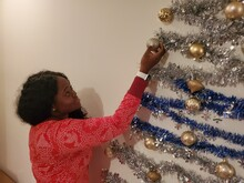 Side View Of Woman Decorating Wall At Home