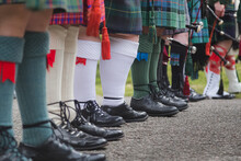 A Row Of Scottish Bagpipers Seen From The Waist Down Show Off Their Tartan Kilts And Traditional Scottish Men's Attire.