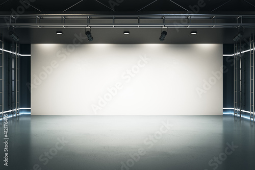 Big blank light screen instead of wall with projectors in empty industrial style hall room with glossy floor Wallpaper Mural