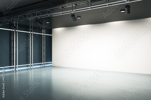 Fotografija Modern spacious industrial style hall with big blank white home cinema screen with projectors, dark glossy floor and glowing led lights on walls