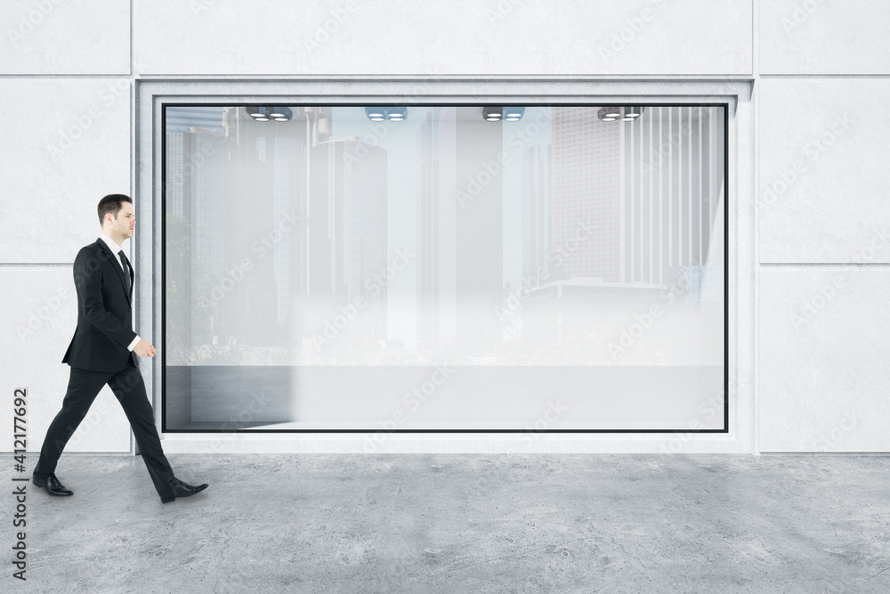 Fototapeta Businessman in black suit goes by huge street shop window with city reflection in modern concrete style building. Mockup