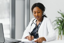 African American Woman Doctor Working At Her Office Online Using Portable Inormation Device. Telemedicine Services. Primary Care Consultations, Psychotherapy, Emergency Services.