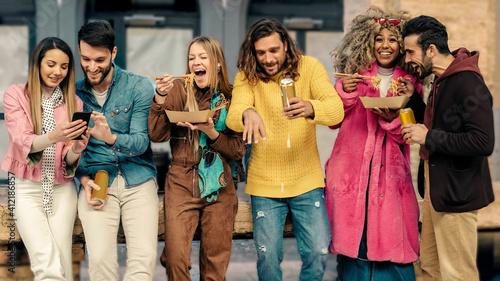 Obraz Gathering of multiracial best friends having fun eating noodles, drinking beers and enjoying friendship together. Positive emotions lifestyle concept. - fototapety do salonu