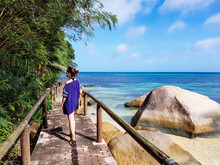 Woman In Beach Coverup Walking On A Wooden Footpath Over A Sandy Golden Beach.