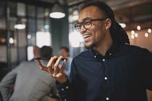 Laughing Businessman Talking On Speakerphone In An Office