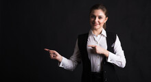 Portrait Of A Businesswoman Who Points Her Finger Towards Copyspace In The Studio On A Black Background
