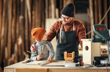 Father and son making bird house in workshop