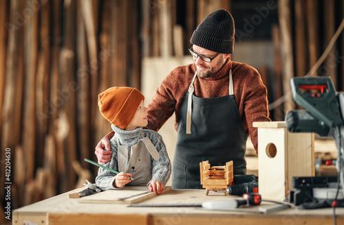 Fototapeta Father and son making bird house in workshop obraz