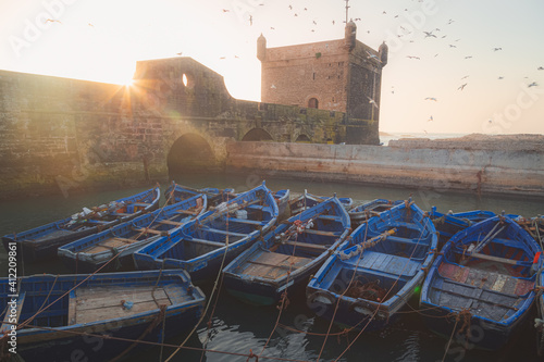 Canvas A clear evening at the historic Scala Harbour at Essaouira Citadel with flocks of seagulls filling the sky and rustic blue fishing boats