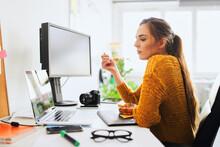 Female Photographer Having Lunch Break Looking On Laptop