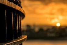 Close-up Of Railing By A River Against Sky During Sunset