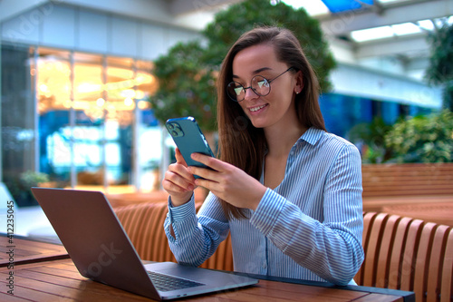 Tela Modern casual smart businesswoman using phone and laptop for remotely working on