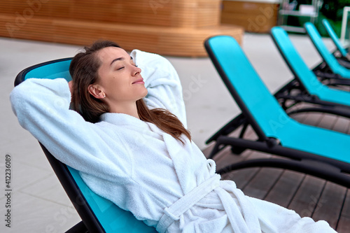 Obraz na plátně Calm serene woman wearing bathrobe with closed eyes and hands behind head relaxing and lying on a lounger at wellness spa resort