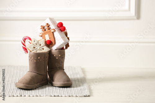 Sweets and gift box in child's boots indoors, space for text Wallpaper Mural
