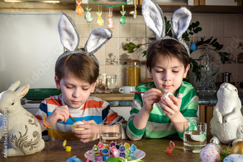 Slika na platnu Two little kid boy coloring eggs for Easter holiday in domestic kitchen, indoors