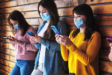 Millennial Girls With Masks On Their Faces Look At Their Phones To View Content On Social Networks - A Group Of Masked Young People Use Smartphones During Covid - Friends And Modern Technologies