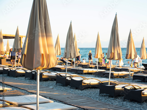 Fotografie, Obraz Empty sun loungers and covered beach umbrellas on an evening pebble beach in Soc