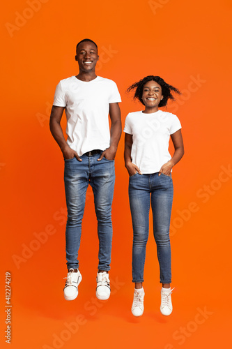 Happy black lovers jumping up with hands in pockets © Prostock-studio