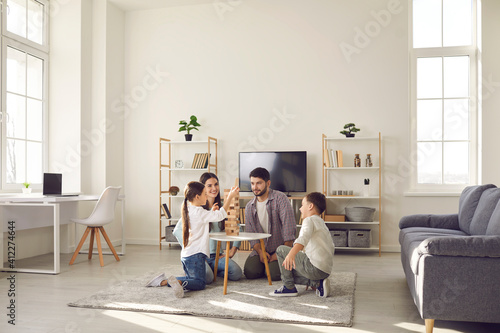 Fototapeta Happy family father mother and two children sitting on floor and playing at home together during weekend
