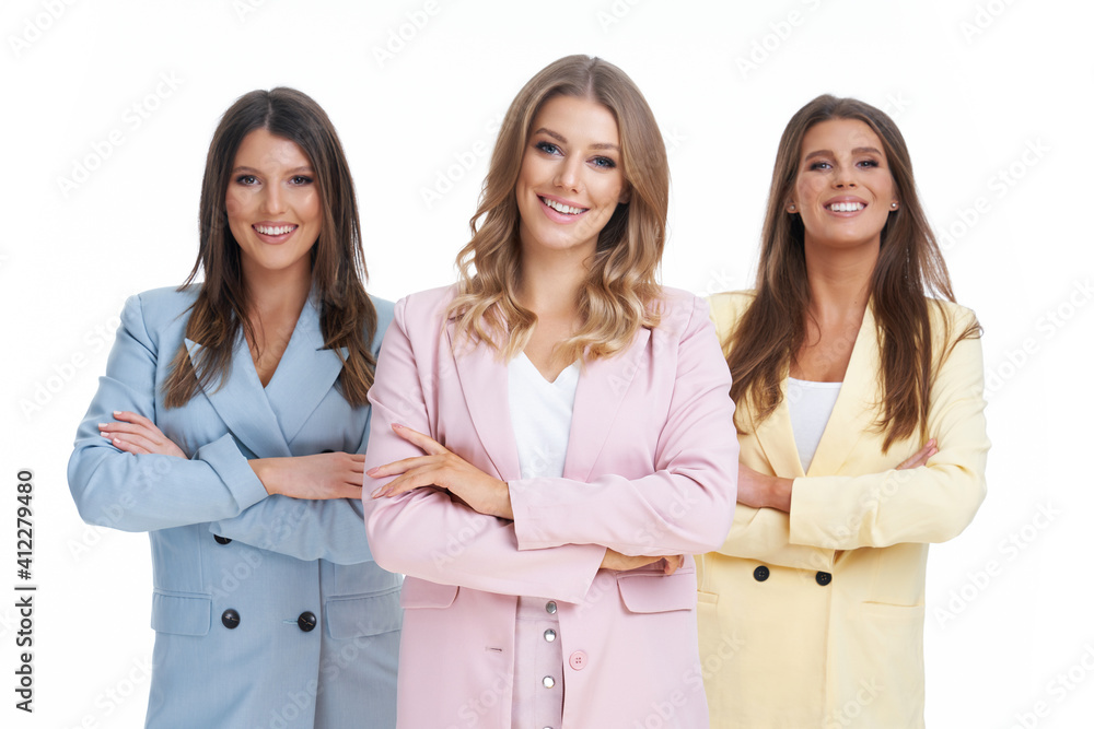 Fototapeta Three women in pastel suits posing over white background