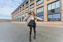 A Girl In A Gray Coat And Black Skirt Is Spinning Against The Backdrop Of A Brick Factory In The City. Bottom View. Wide Angle.