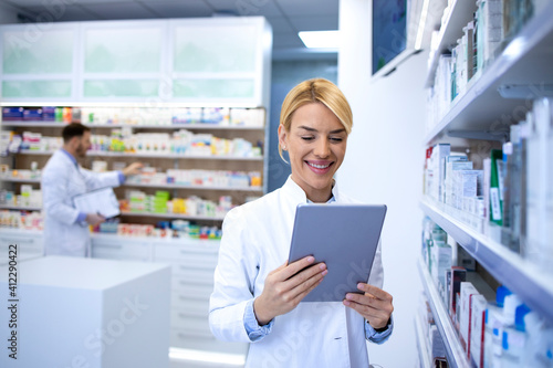 Portrait of female experienced pharmacist working on tablet in pharmacy store by the shelf with medicines Wallpaper Mural