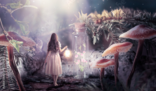 Fototapeta Girl in dress with shining lantern in hand walking in fantasy fairy tale elf forest, ghost blooming rose flower locked in bottle and moon rays, mysterious fir tree and mushrooms in magical elvish wood obraz