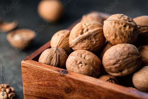 Obraz na plátně Close-up of walnuts in a shell in a wooden box on a table.