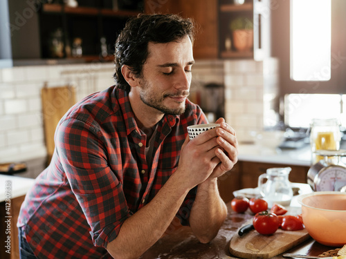 Obraz Handsome man preparing breakfast at home. Young man drinking coffee and enjoying in the morning.. - fototapety do salonu