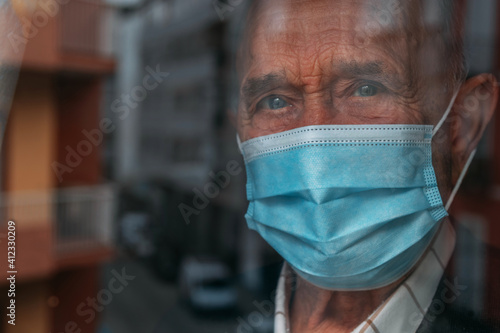 elderly man with face mask looking out the window in pandemic quarantine