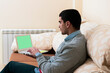 young man is doing looking for things on the internet with his laptop on the sofa in his apartment