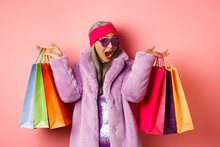 Stylish Asian Senior Woman Going Shopping, Wearing Trendy Clothes And Sunglasses, Holding Store Bags With Gifts, Treat Yourself Concept, Pink Background
