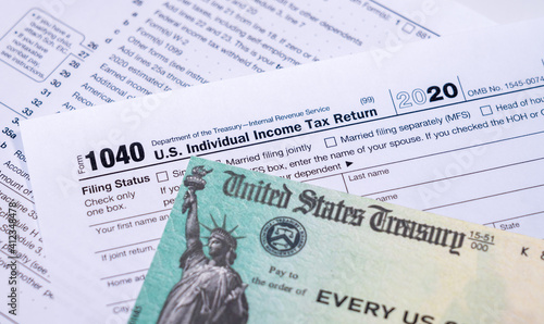 US Treasury stimulus check laying on a form 1040 tax return for 2020 to illustrate questions about qualification for payment © steheap
