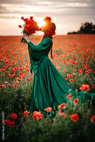 Obraz A young red-haired woman in a wreath stands in a blooming poppy field in the sun. Full-length portrait. - fototapety do salonu
