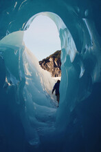 View From A Blue Colored Ice Crevice, With A Silhouetted Man Exiting The Tunneled Structure Towards The Sunlit Wintery Landscape.