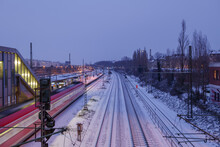 Night Outdoor Scenery And Top View Over Platform Railway Station, Railway Track Covered By Snow, And Motion Of Regional Train In Düsseldorf, Germany In Winter Season.